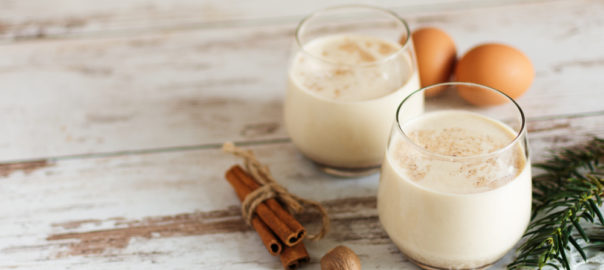 Glasses of lactose free eggnog with cinnamon and eggs
