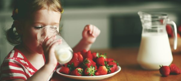Young girl enjoying a glass of lactose free milk and strawberries