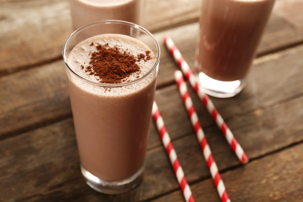 Chocolate lactose free milkshake in glass with cocoa and straws