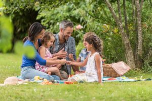 family enjoying afternoon picnic outside in the spring