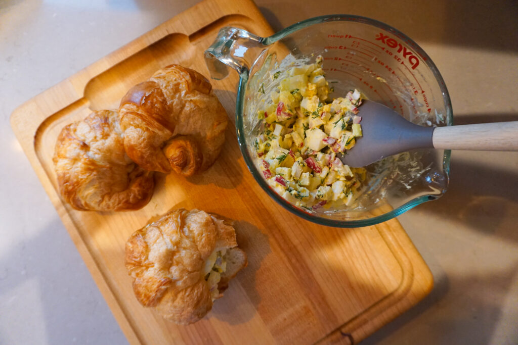 egg salad croissant sandwiches on wooden cutting board
