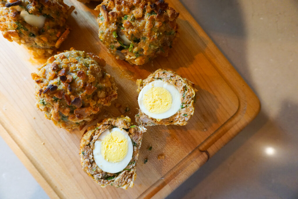 sausage wrapped hard boiled eggs, scotch eggs, cut open on wooden cutting board