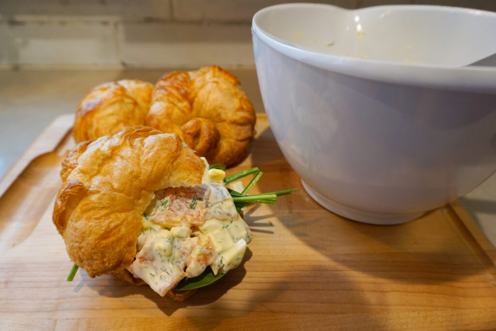 smoked salmon egg salad croissant sandwiches on wooden cutting board with white mixing bowl