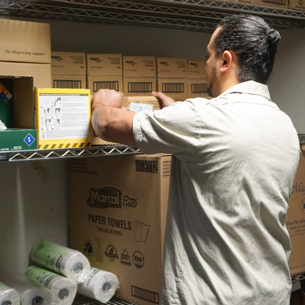 man in utility closet taking inventory