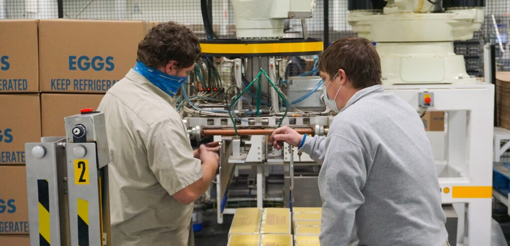 two men inspecting and fixing robotic packaging equipment