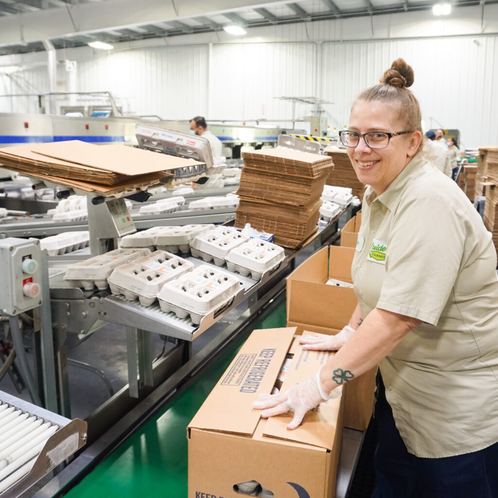 woman smiling and closing egg box in processing facility