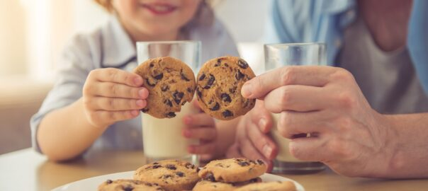 dad and son enjoying chocolate chip cookies and white milk