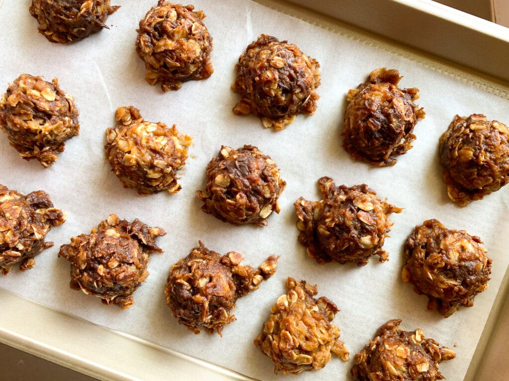 chocolate peanut butter oatmeal ball bites on parchment lined baking sheet