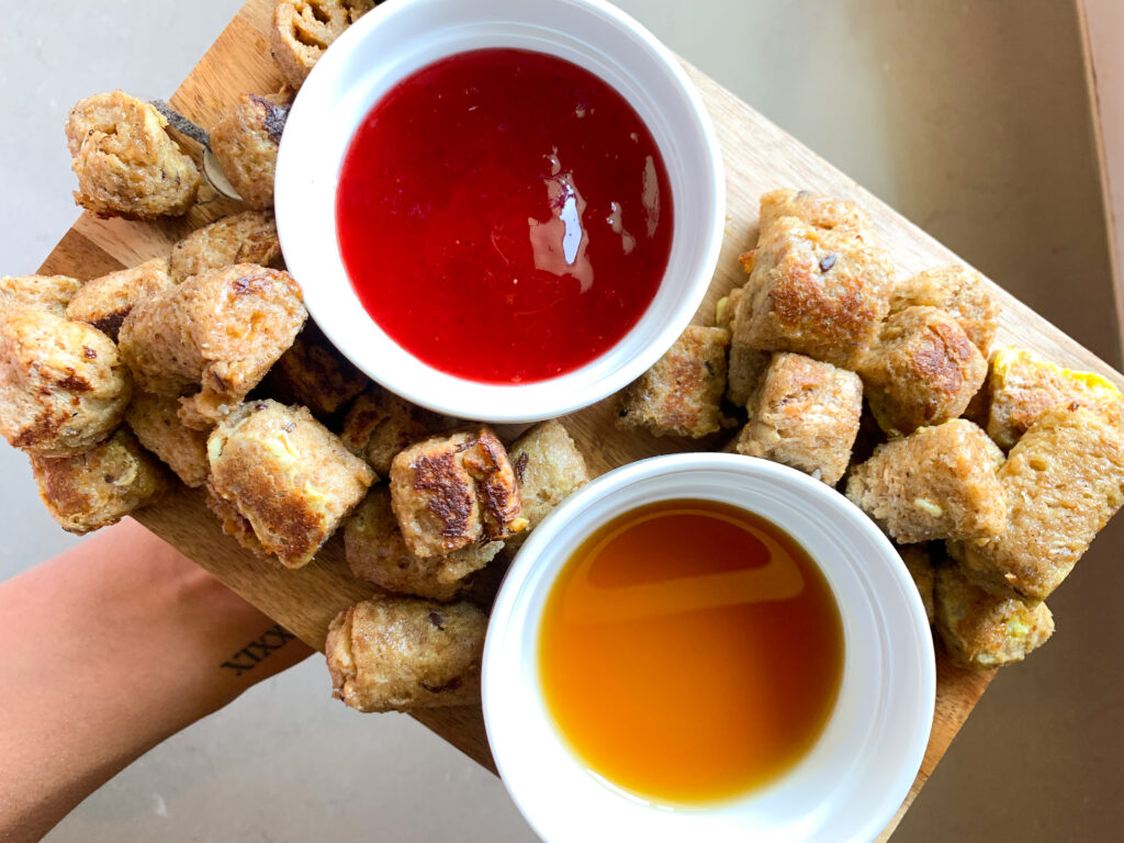 peanut butter french toast roll ups plated with maple syrup and jelly