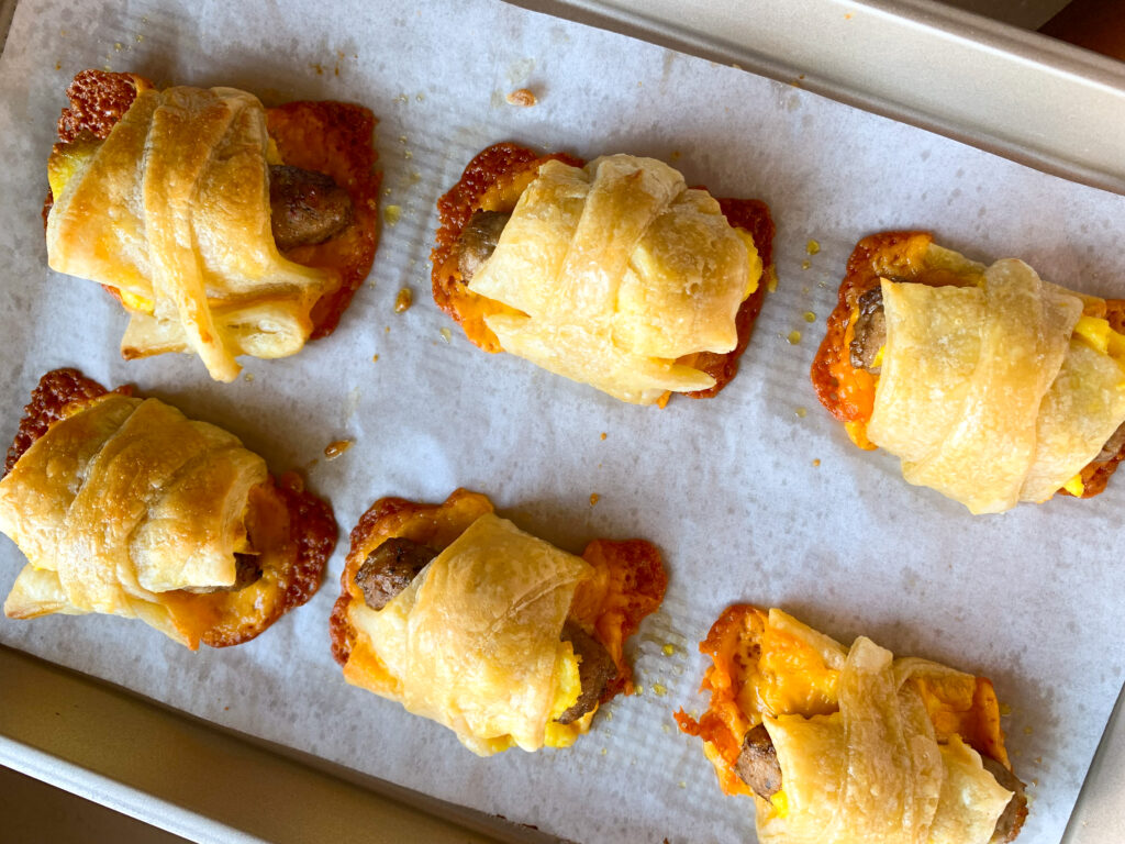 sausage, egg & cheese rolls up on parchment lined baking sheet