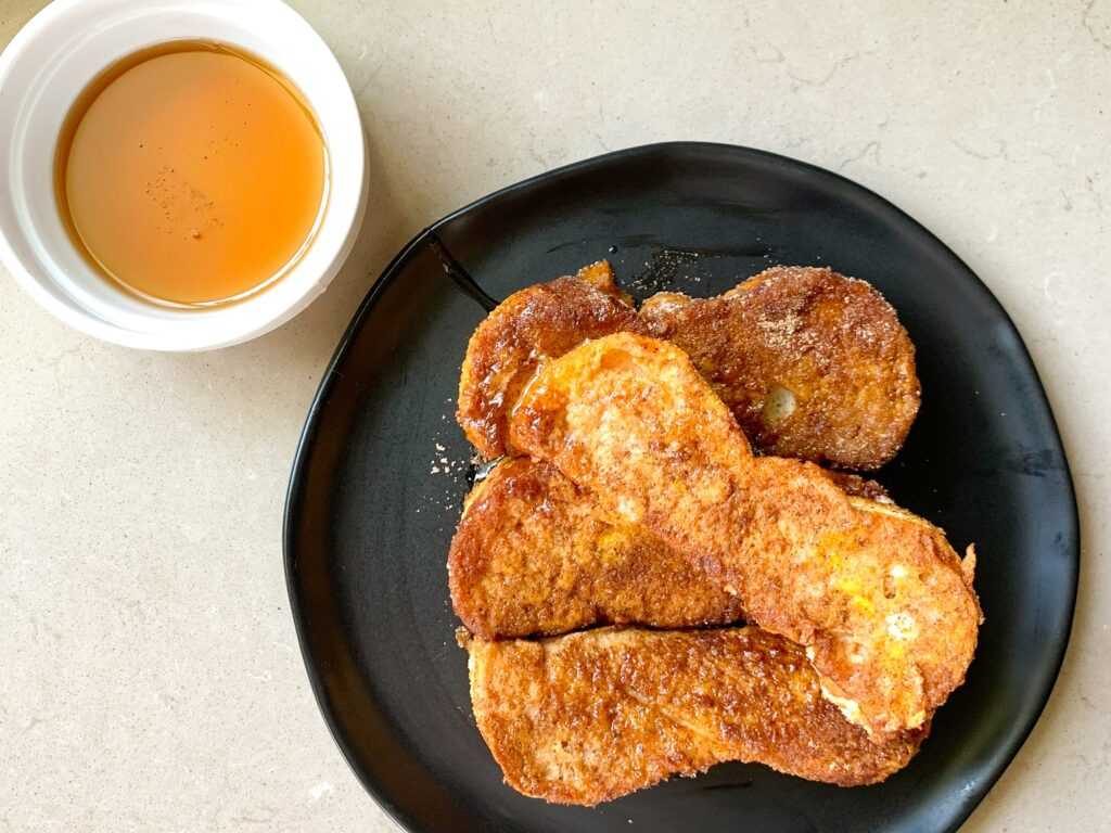 pumpkin french toast sticks plated with maple syrup dipping cup