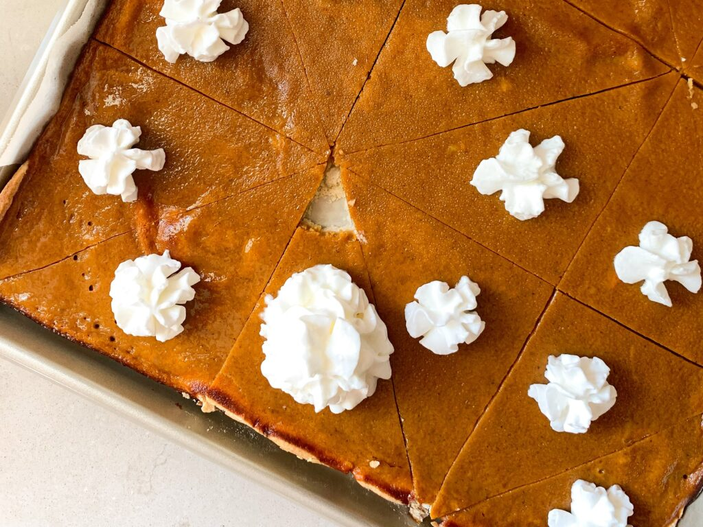 sheet pan pumpkin pie in baking tray with whipped cream